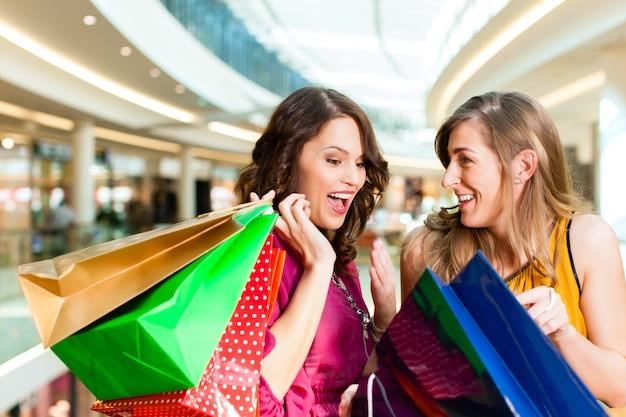 Chicas de compras en el centro comercial buscando en bolsas