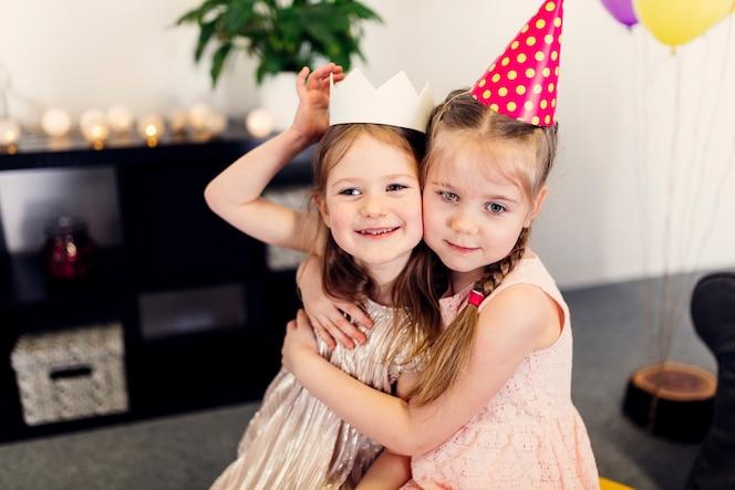 Chicas con gorras de colores abrazándose