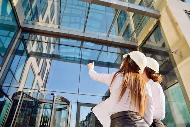 Chicas en la construcción de cascos blancos con tabletas en las manos