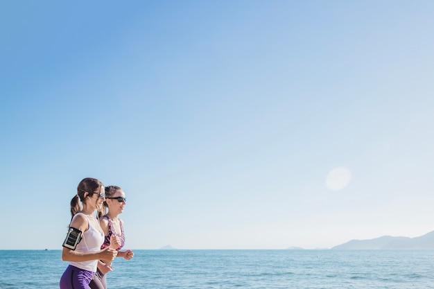 Chicas corriendo con el mar de fondo