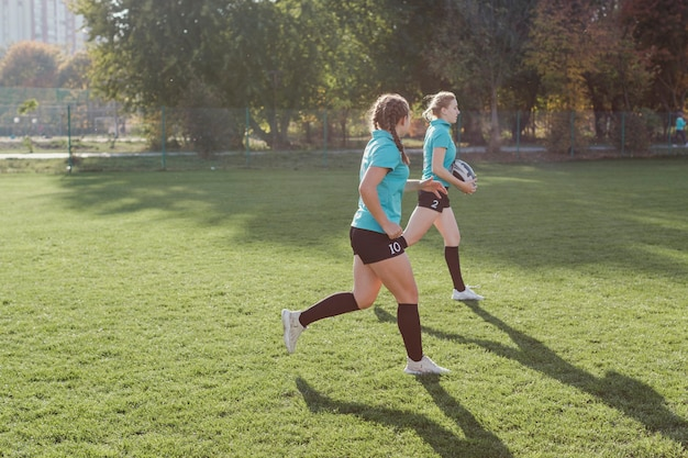 Chicas corriendo con una pelota de rugby