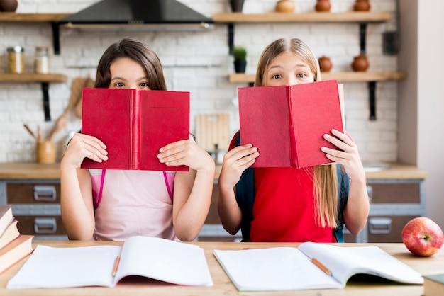 Chicas cubriendo caras con libros.