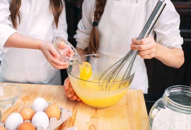 Chicas divertidas niños están preparando la masa en la cocina.