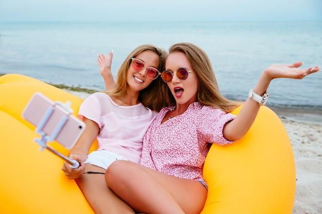 Chicas divertidas posando en la cámara mientras toma una selfie en el teléfono inteligente, sentado en el sofá de aire lamzac