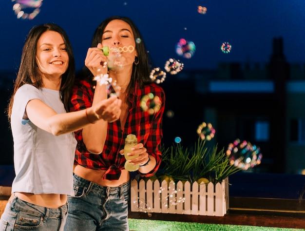 Chicas divirtiéndose con pompas de jabón y fuegos artificiales