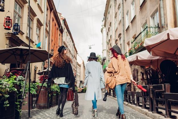 Chicas divirtiéndose tiro al aire libre de tres mujeres jóvenes caminando en la calle de la ciudad. vista trasera