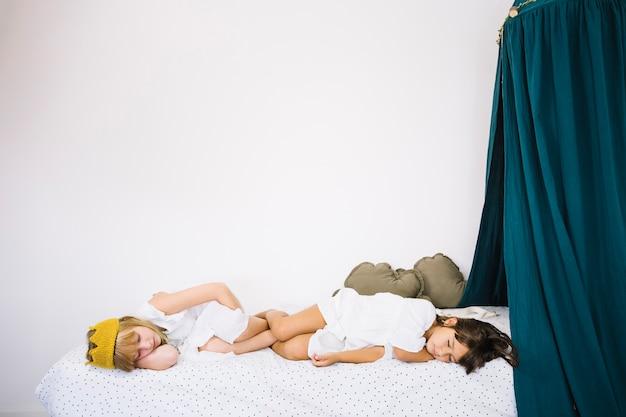 Chicas durmiendo en la cama con cortinas
