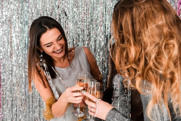 Chicas elegantes brindando con champagne