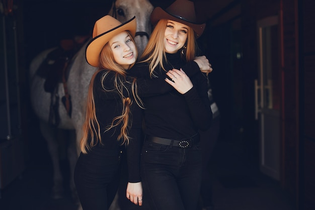 Chicas elegantes con un caballo en un rancho.
