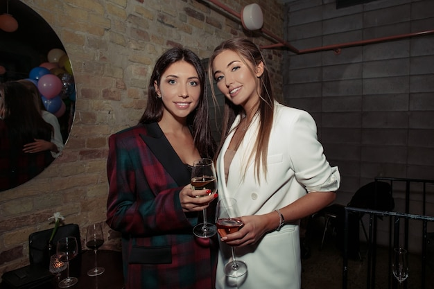 Chicas elegantes divirtiéndose en una fiesta. rubia con chaqueta blanca y accesorios, maquillaje natural en la cara y cabello elegante. mujer morena con un vestido negro de moda