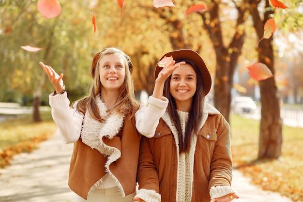 Chicas elegantes y con estilo en un parque de otoño
