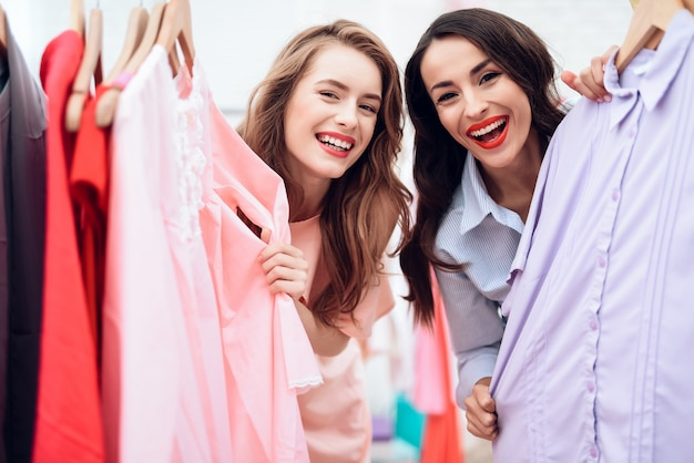 Las chicas eligen la ropa en la tienda de moda.