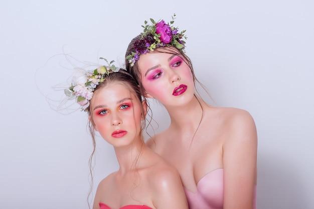Chicas encantadoras con maquillaje moderno y atrevido y flores frescas.