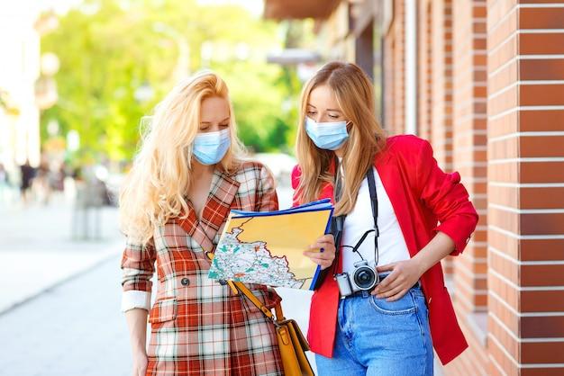 Chicas con estilo mirando en el mapa turístico de la ciudad