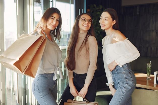 Chicas con estilo de pie en una cafetería con bolsas de compras