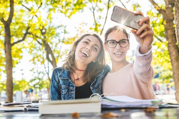 Chicas estudiando y tomando una selfie divertida en el parque.
