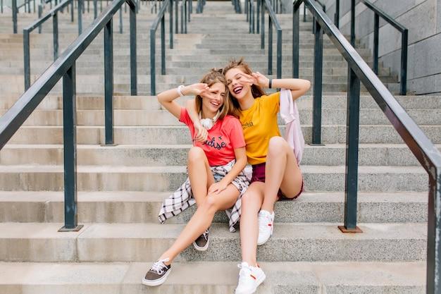 Chicas extasiadas disfrutando de un buen día juntos posando con el signo de la paz y una hermosa sonrisa