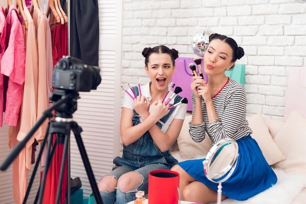 Las chicas falsas levantan muchos pinceles a la cámara.