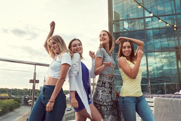 Chicas felices bailan en una fiesta en la terraza