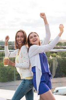 Chicas felices bailando espalda con espalda