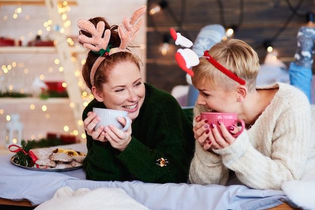 Chicas felices bebiendo té o café caliente en la cama