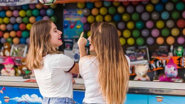 Chicas felices divirtiéndose en el parque de atracciones