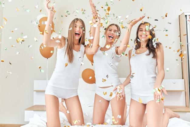 Chicas con fiesta con confeti en el dormitorio.