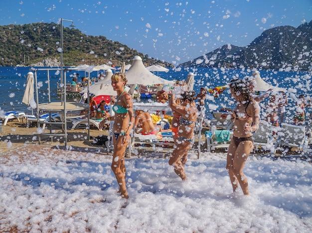 Chicas en una fiesta en la playa con pompas de jabón.