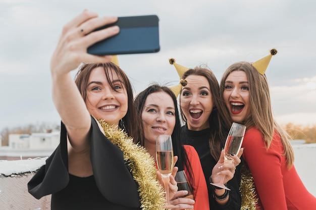 Chicas fiesteras tomando selfie grupal en la azotea