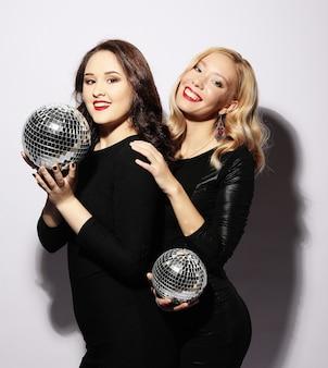 Chicas fiesteras en vestido negro con bolas de discoteca