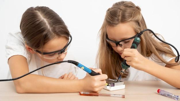 Chicas con gafas protectoras haciendo experimentos científicos.