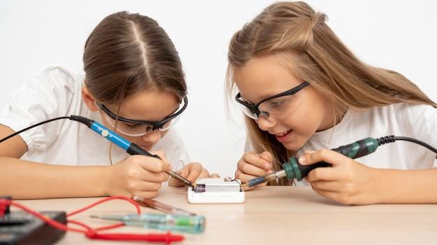 Chicas con gafas de seguridad haciendo experimentos científicos juntos.