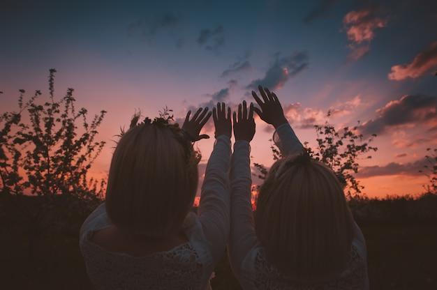 Chicas gemelas estirando las manos hacia el cielo.