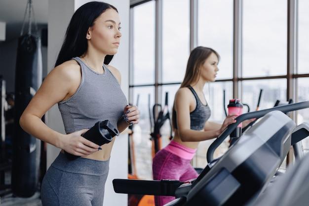 Las chicas en el gimnasio están entrenadas en cintas de correr y beben agua, sonriendo.
