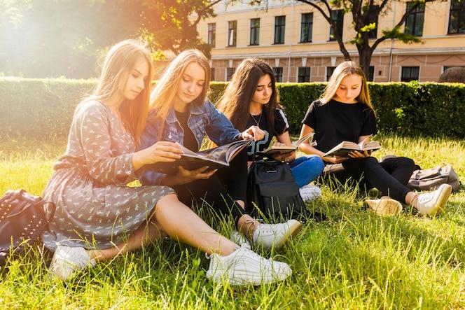 Chicas guapas adolescentes leyendo en el parque
