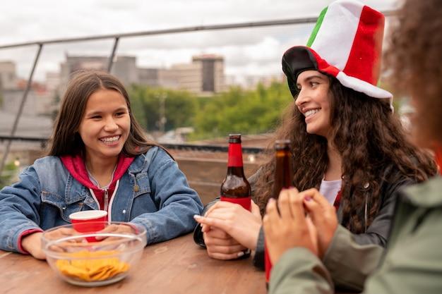 Chicas guapas alegres con bebidas sentadas a la mesa después del partido de fútbol y charlando sobre su equipo favorito