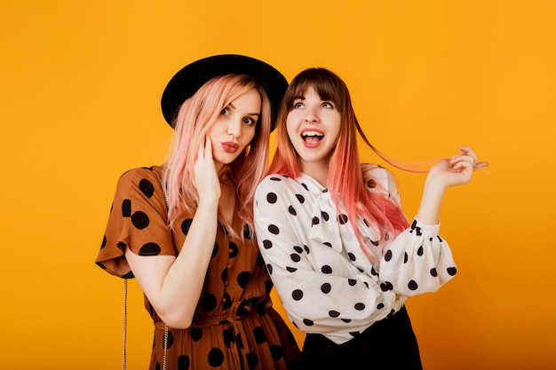 Chicas guapas con cara emocional posando sobre pared amarilla