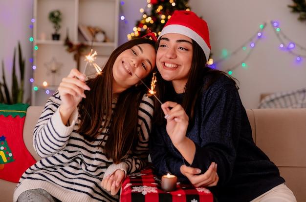 Chicas guapas complacidas con gafas de reno y gorro de papá noel sosteniendo y mirando bengalas sentados en sillones y disfrutando de la navidad en casa