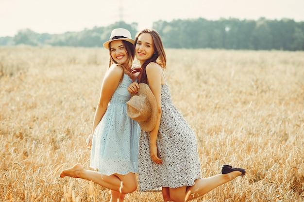 Las chicas guapas descansan en un campo.