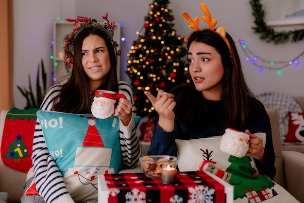 Chicas guapas disgustadas con corona de acebo y diadema de renos sostienen tazas y miran de lado sentadas en sillones y disfrutando de la navidad en casa