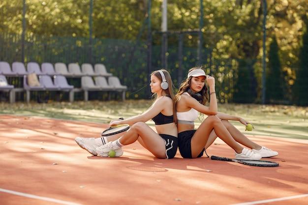Chicas guapas y elegantes en la cancha de tenis