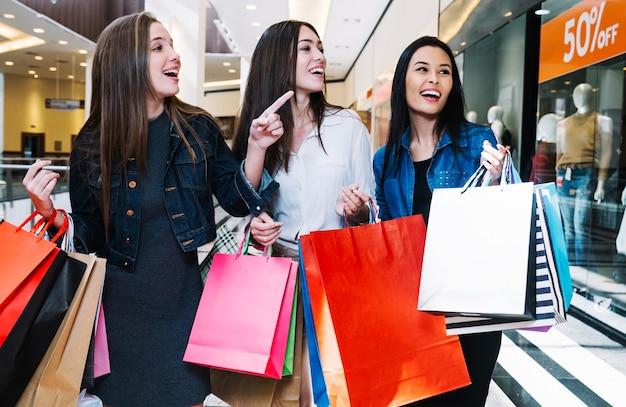 Chicas guapas explorando tiendas en el centro comercial