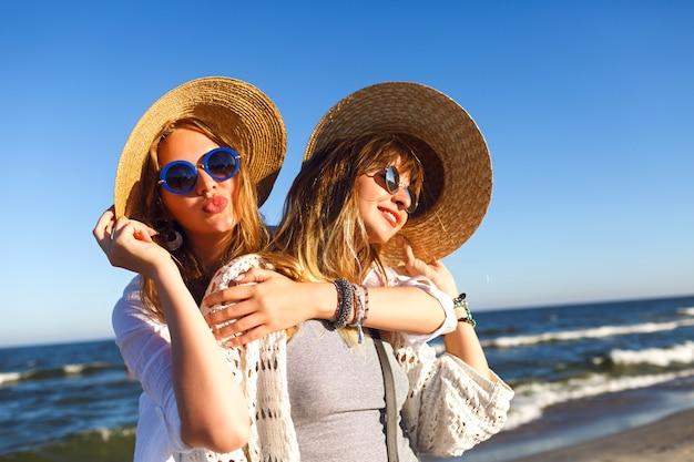 Chicas guapas haciendo selfie y enviando besos al aire a la cámara, viajes de verano, ropa boho, gafas de sol y sombreros de paja
