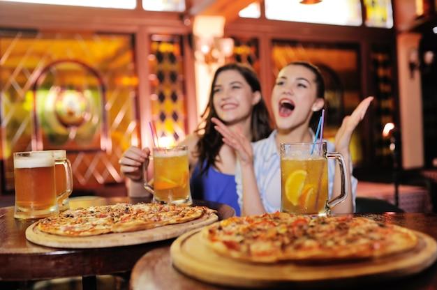Chicas guapas jóvenes comiendo pizza, bebiendo cerveza o un cóctel de cerveza y viendo fútbol