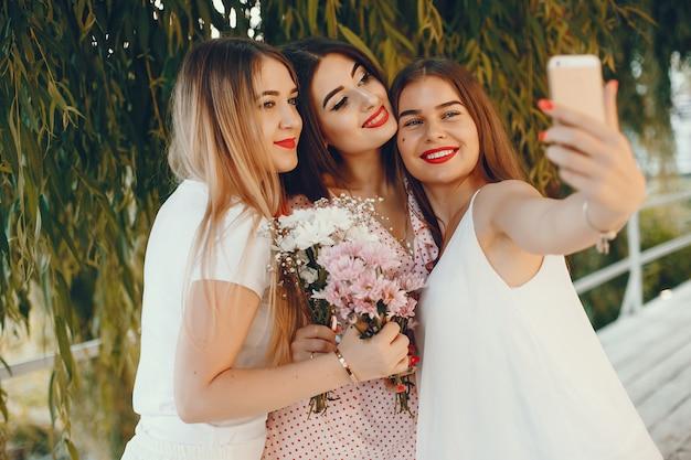 Chicas guapas en un parque de verano con un teléfono.
