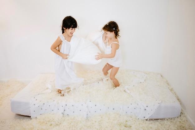 Las chicas guapas que tienen almohadas luchan en el colchón