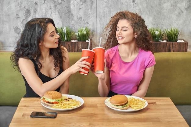 Chicas guapas sentado en la cafetería y tintinear vasos de papel.