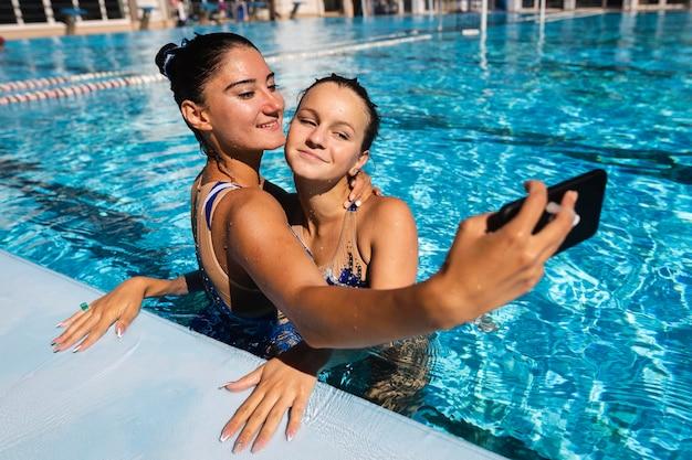 Chicas guapas tomando un selfie en la piscina