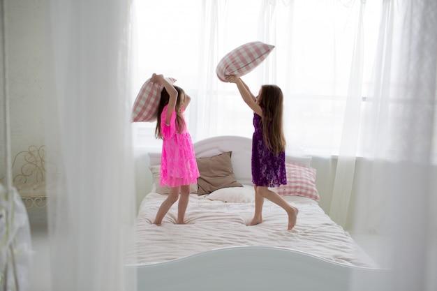 6afee45438 Chicas guapas en vestidos de color rosa y púrpura tienen pelea de cojines.
