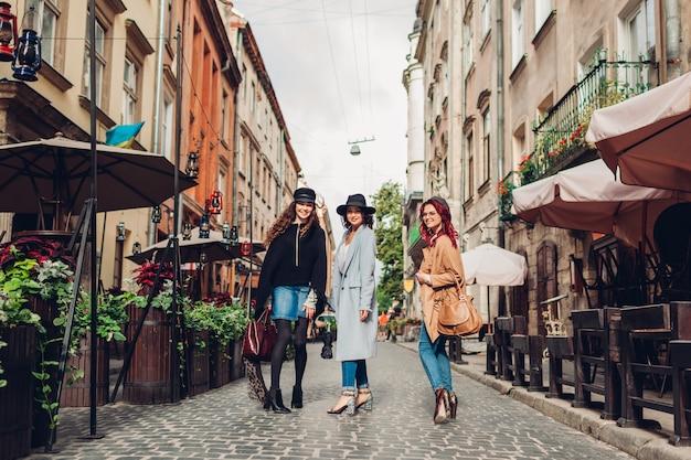 Chicas hablando y divirtiéndose. tiro al aire libre de tres mujeres jóvenes caminando en la calle de la ciudad.
